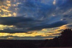 L'arrangement de Sun dans un nuage de tempête a couvert le ciel de fin d'été Photographie stock