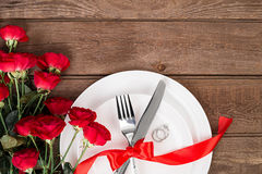 L'arrangement de table de dîner de Saint-Valentin avec le ruban rouge, les roses, le couteau et la fourchette sonnent au-dessus d Photos stock