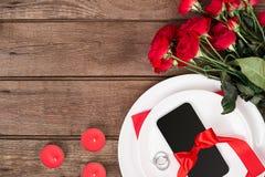 L'arrangement de table de dîner de Saint-Valentin avec le ruban rouge, les roses, le couteau et la fourchette sonnent au-dessus d Photo stock