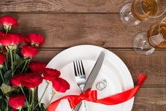 L'arrangement de table de dîner de Saint-Valentin avec le ruban rouge, les roses, le couteau et la fourchette sonnent au-dessus d Photo libre de droits
