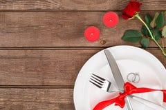 L'arrangement de table de dîner de Saint-Valentin avec le ruban rouge, a monté, couteau et anneau de fourchette au-dessus de fond Image libre de droits
