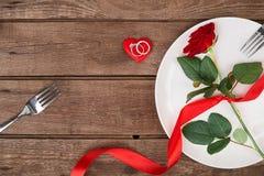 L'arrangement de table de dîner de Saint-Valentin avec le ruban rouge, a monté, couteau et anneau de fourchette au-dessus de fond Photographie stock libre de droits