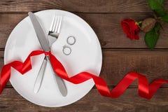 L'arrangement de table de jour de valentines avec le plat, fourchette, couteau, anneau, ruban et a monté Fond Photo stock