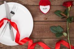 L'arrangement de table de jour de valentines avec le plat, fourchette, couteau, anneau, ruban et a monté Fond Images libres de droits