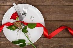 L'arrangement de table de jour de valentines avec le plat, fourchette, couteau, anneau, ruban et a monté Fond Photos libres de droits