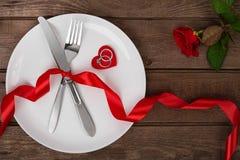 L'arrangement de table de jour de valentines avec le plat, fourchette, couteau, coeur rouge, anneau, ruban et a monté Fond Image stock
