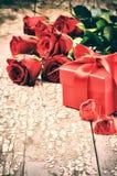 L'arrangement de Valentine avec le bouquet des roses rouges et du présent Photo libre de droits