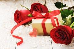 L'arrangement de Valentine avec le bouquet des roses rouges et du présent Image libre de droits