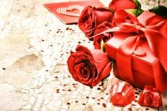 L'arrangement de Valentine avec le bouquet des roses rouges et du présent Photographie stock libre de droits