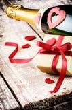 L'arrangement de Valentine avec le présent et la bouteille de champagne Images libres de droits