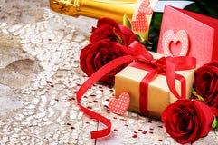 L'arrangement de Valentine avec le présent et le bouquet des roses rouges Photographie stock