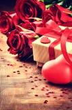 L'arrangement de Valentine avec les roses rouges et le présent Photographie stock libre de droits