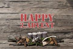 L'arrivo della decorazione di Buon Natale che brucia la candela grigia ha offuscato il englisch terzo del messaggio di testo del  Fotografie Stock Libere da Diritti
