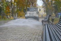 L'arrosage en automne de la voiture monte en parc et lavages de l'eau Photos stock