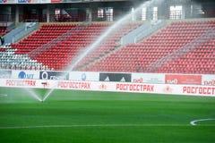 L'arroseuse de l'eau arrose le terrain de football Photos stock