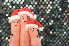 L'art de doigts de la famille célèbre Noël Concept du groupe de personnes souriant dans des chapeaux de nouvelle année Images stock