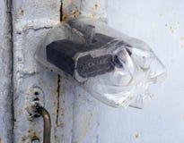 L'arte della bottiglia di plastica protegge la serratura di porta del garage di precipitazione Immagine Stock