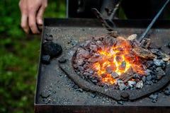 L'article chaud est inséré dans la forge de forgerons de laquelle les langues de la flamme Concept : blacksmithing, forge images stock