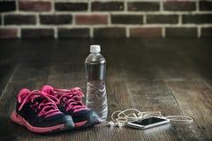 L'article de sport courant de forme physique, espadrilles arrosent la musique de téléphone, il Image stock