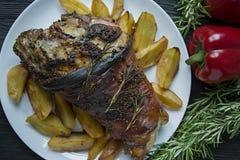 L'articulation frite de porc avec des pommes de terre a servi d'un plat blanc A d?cor? du poivre bulgare frais, romarin Fond en b image stock