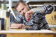 L'artigiano archiva il collo di legno della chitarra in officina Fotografia Stock Libera da Diritti