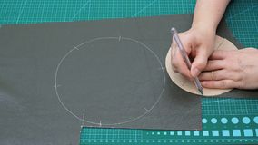 L'artigiano disegna il taglio del modello delle tasche del sacchetto facendo uso di forma di carta video d archivio