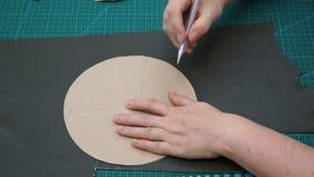L'artigiano disegna il taglio del modello del fondo del sacchetto facendo uso del modello della carta video d archivio
