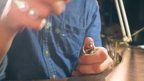 L'artigiano sta utilizzando gli strumenti del metallo per lucidare un anello video d archivio