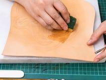 L'artisan amortit le modèle sur le cuir images libres de droits