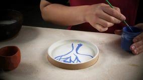 L'artisan d?core un plat nouvellement fabriqu? de peinture Travail dans l'atelier banque de vidéos