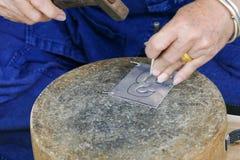 L'artisan découpe l'art de plat argenté Photographie stock libre de droits