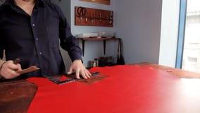 L'artisan fait une ligne des inscriptions sur le tissu en cuir rouge banque de vidéos