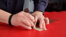 L'artisan fait une ligne des inscriptions sur le tissu en cuir rouge clips vidéos