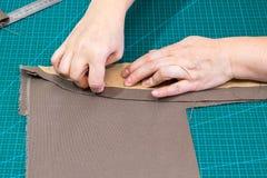 L'artisan goupille le modèle aux matériaux image libre de droits
