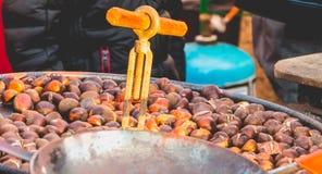 L'artisan grille des châtaignes sur un marché de Noël Photos stock