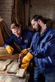 l'artisan indiquant l'associé dans les gants protecteurs et google le travail avec la perceuse électrique photos stock