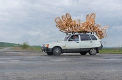 L'artisan transporte la vannerie sur un toit d'une petite voiture Photos libres de droits