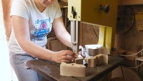 L'artisane coupe un objet de voitures de jouet en bois de bois avec la scie à ruban banque de vidéos