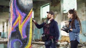 L'artista barbuto attraente dei graffiti del tipo sta parlando con sua giovane donna graziosa dello studente serio e sta insegnan stock footage