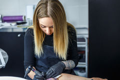L'artista biondo disegna un tatuaggio con concentrazione massima Fotografia Stock