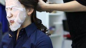 L'artista dell'acconciatura rende la procedura del ferro di arricciatura dei capelli per la donna castana stock footage