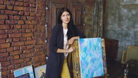 L'artista della giovane donna con le pitture dell'acquerello sta vicino all'immagine finita e sorride nella macchina fotografica fotografia stock