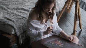 L'artista della ragazza dipinge un'immagine nello studio domestico impianti del pittore nelle prime ore del mattino video d archivio