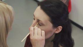 L'artista di trucco applica l'ombra di occhio Bello fronte della donna Trucco perfetto Orli Ombretto cosmetico Dettaglio di trucc stock footage
