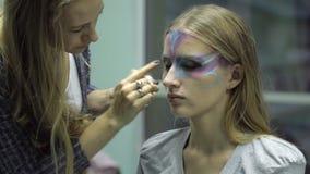 L'artista dipinge il fronte di modello con i vari bei colori, fine su archivi video
