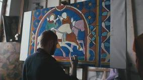 L'artista dipinge una finestra di vetro macchiato medievale video d archivio