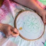L'artista disegna il contorno del fiore su batik fotografie stock