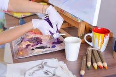 L'artista espelle pittura dai tubi sulla tavolozza per i colori mescolantesi t Fotografie Stock Libere da Diritti