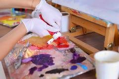 L'artista espelle pittura dai tubi sulla tavolozza per i colori mescolantesi t Immagini Stock Libere da Diritti