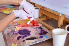L'artista espelle pittura dai tubi sulla tavolozza per i colori mescolantesi t Fotografia Stock